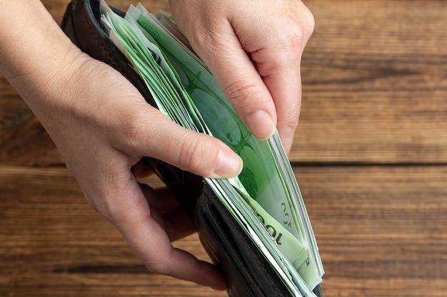 Handen met portemonnee vol met 100 euro-bankbiljetten