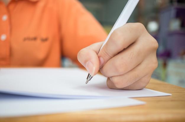 Handen met potlood over aanvraagformulier studenten die examens afleggen