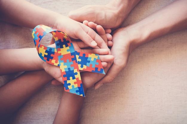 Handen met puzzel lint voor autisme bewustzijn