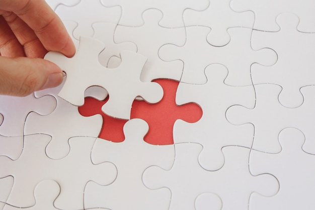Handen met puzzelstukken, bedrijfsstrategieplanning