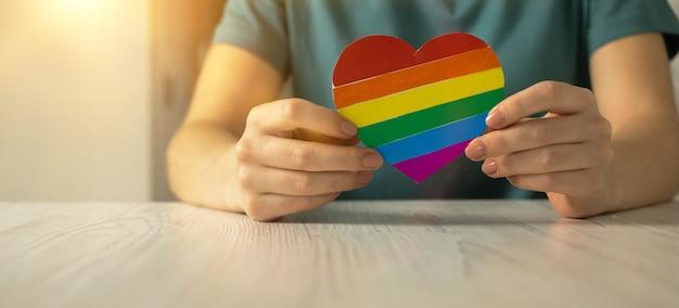 Handen met regenboog kleur vlag in hartvorm, symbool van lgbt pride maand vieren, gemeenschap van homo's, lesbiennes, biseksuelen en transgenders, mensenrechten concept foto