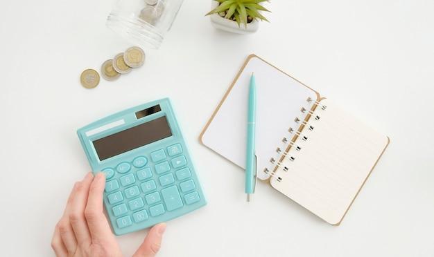 Handen met rekenmachine, munten en pen op witte tafel. bovenaanzicht