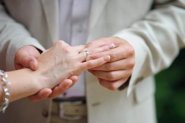 Handen met ringen bruidegom die gouden ring op de vinger van de bruid zetten tijdens huwelijksceremonie