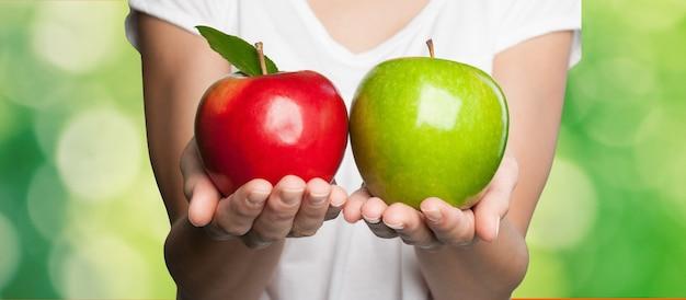 Handen met rode en groene appels