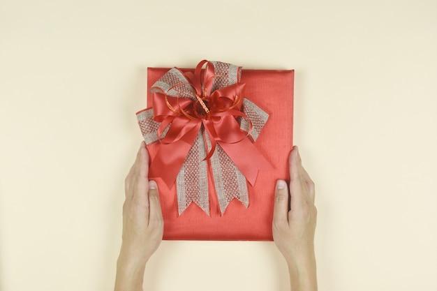 Handen met rode geschenkdoos aanwezig voor verjaardag valentijn dag kerst nieuwjaar concept