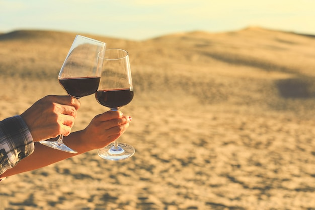 Handen met rode wijnglazen op dune of pyla tijdens zonsondergang