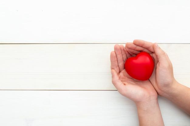 Handen met rood hart, gezondheidszorg, liefde, valentijn, hulpeloos, schenking, opmerkzaamheid, welzijn