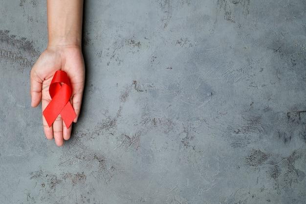 Handen met rood lint, hiv-bewustzijnsconcept, wereldaidsdag, wereldhypertensiedag