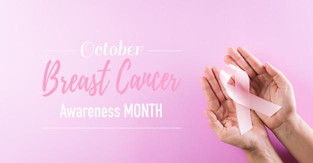 Handen met roze linten, borstkanker bewustzijn concept.