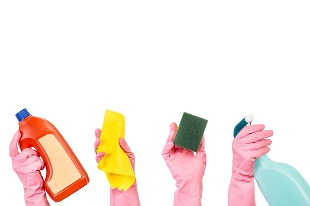 Handen met roze rubberen handschoenen met flessen reinigingsproduct en reinigingselementen op een witte achtergrond