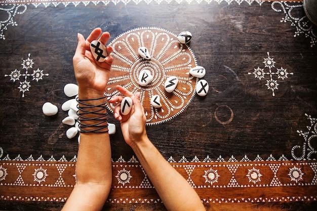 Handen met runenstenen op een sierlijke tafel