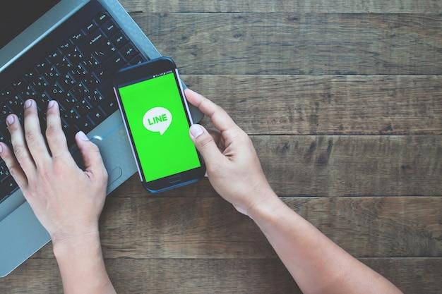 Handen met samsung mobile geopend voor line-applicatie.