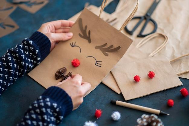 Handen met schattige rendieren versierde papieren kerstzak