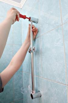 Handen met schroevendraaier bevestigd aan wand douchekop glijrail met zeepschaal.