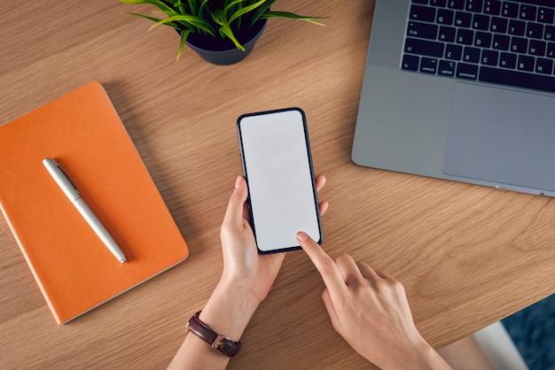 Handen met smartphone met leeg scherm, laptop met boek en accessoires op houten tafel.