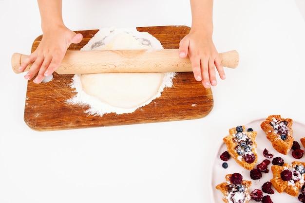 Handen met speld en duff, zoete cakes met bessen in hoek
