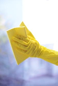 Handen met spray die het raam schoonmaken