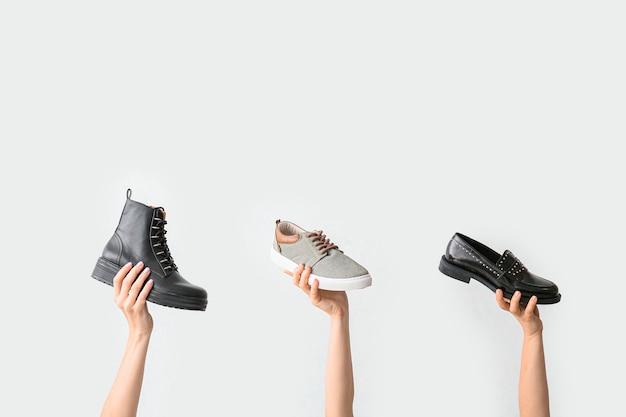 Handen met stijlvolle schoenen op wit oppervlak
