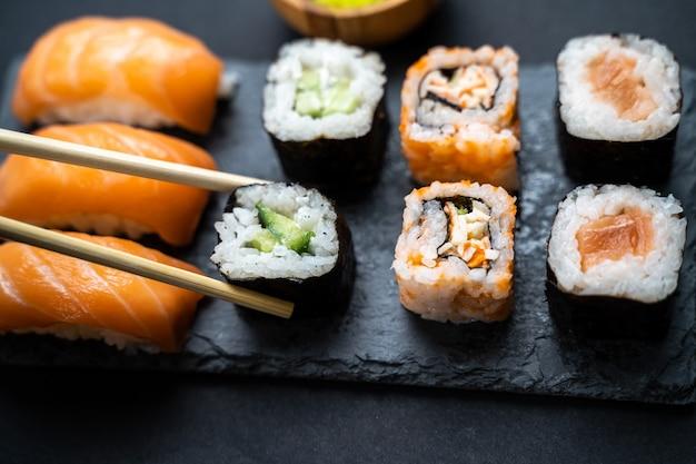 Handen met stokken die een sushimaki houden