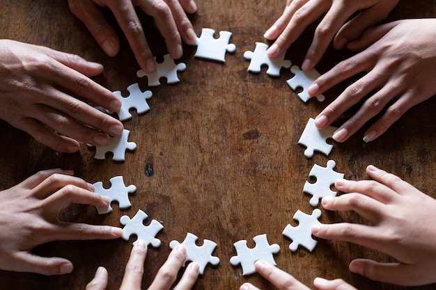 Handen met stuk van de lege puzzel op zwarte achtergrond