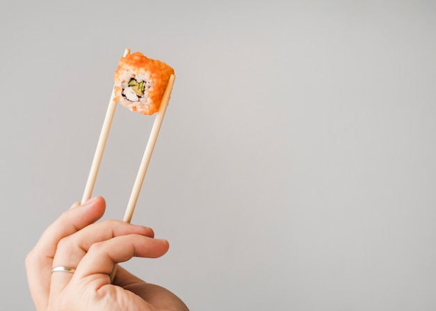 Handen met sushi roll met stokjes kopie ruimte