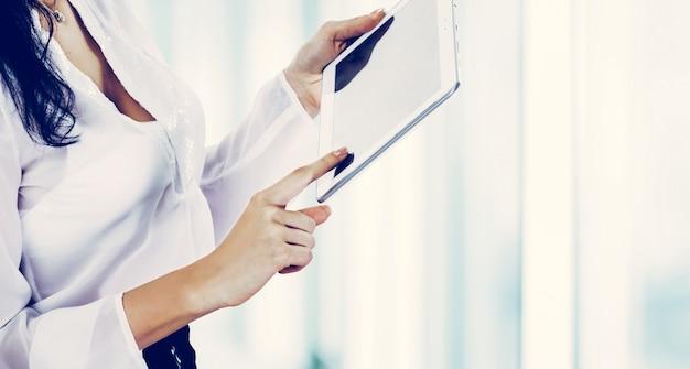 Handen met tablet close-up, wijsvinger drukt op een lege scre