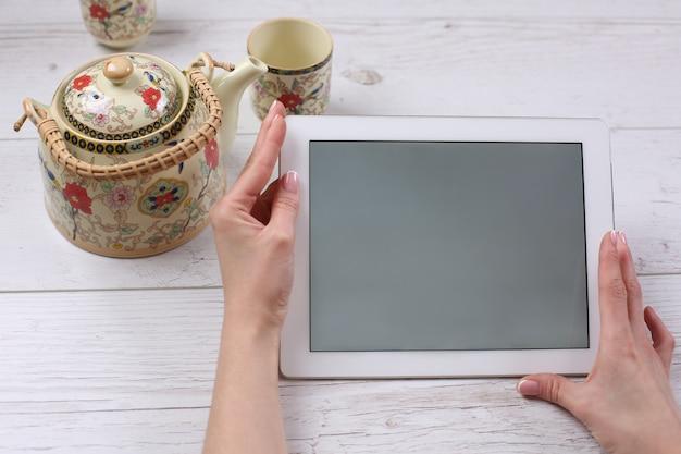 Handen met tablet op houten tafel met thee