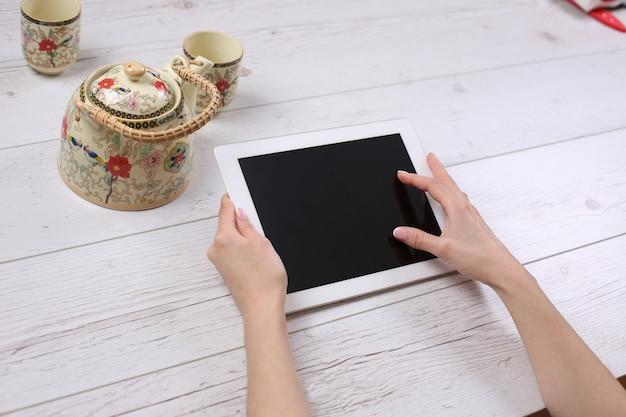 Handen met tablet vergelijkbaar met ipades-stijl op houten tafel met thee