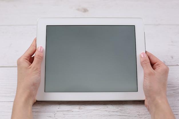 Handen met tablet vergelijkbaar met ipades-stijl op houten tafel