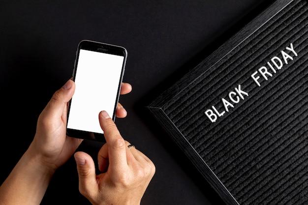 Handen met telefoon mock up naast zwart vrijdag tapijt