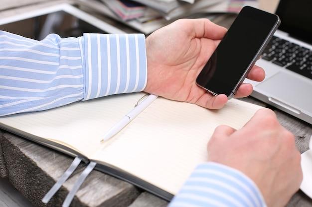 Handen met telefoon op houten tafel met tablet