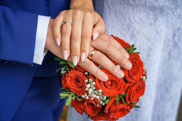 Handen met trouwringen op het boeket van de bruid