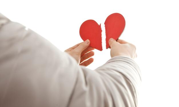 Handen met twee delen van een gebroken hart
