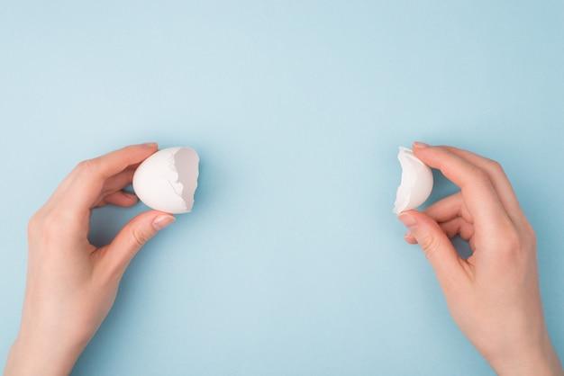 Handen met twee helften van gebarsten eieren