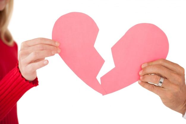 Handen met twee helften van gebroken hart