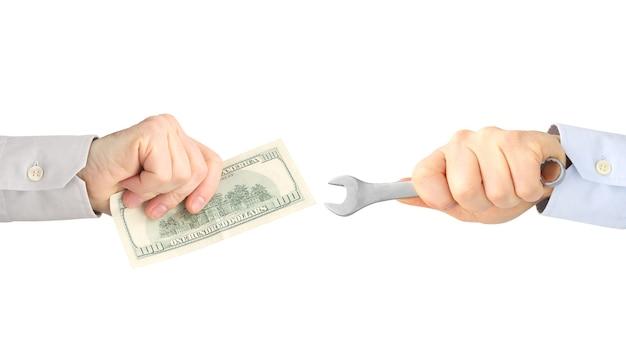 Handen met uitrustingsstuk en geld op een witte achtergrond. salaris. zakenrelatie.