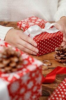 Handen met verpakt aanwezig op een houten tafel close-up