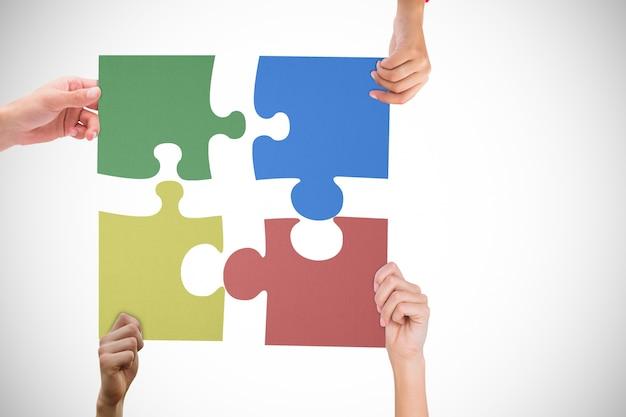 Handen met verschillende stukjes van een puzzel