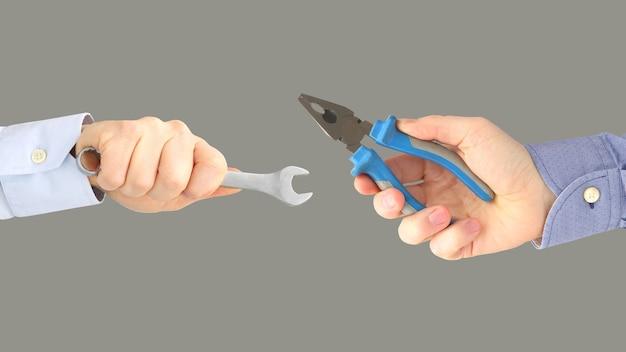 Handen met verschillende werkende hulpmiddelen geïsoleerd