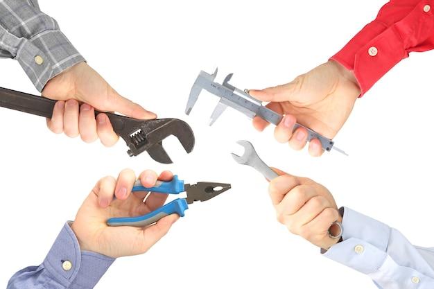 Handen met verschillende werkende hulpmiddelen op wit. industrie en industriële ondernemingen. werkend beroep.