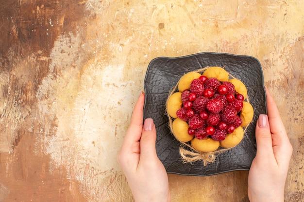 Handen met versgebakken cake van de gift op een bruine plaat op gemengde kleurentafel