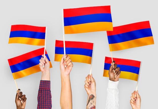 Handen met vlaggen van armenië zwaaien