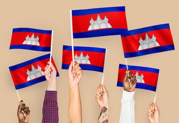 Handen met vlaggen van cambodja zwaaien