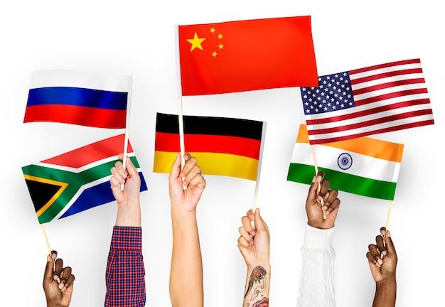 Handen met vlaggen van china, duitsland, india, zuid-afrika en rusland