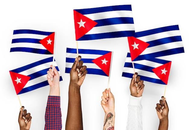 Handen met vlaggen van cuba zwaaien