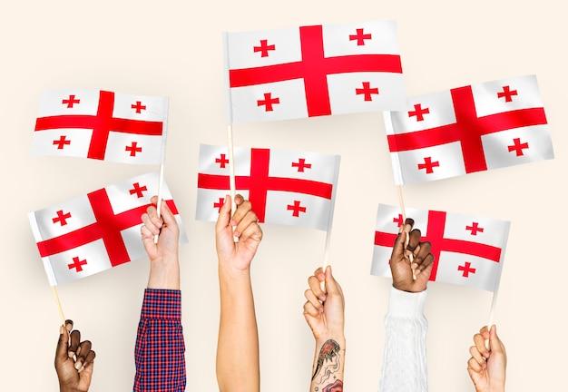 Handen met vlaggen van georgië zwaaien