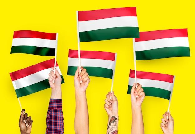 Handen met vlaggen van hongarije zwaaien