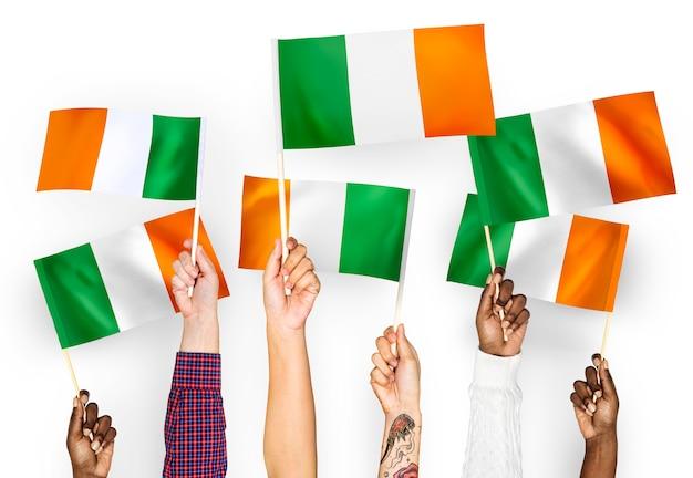 Handen met vlaggen van ierland zwaaien