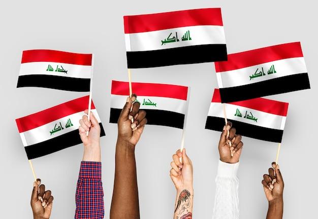 Handen met vlaggen van irak zwaaien