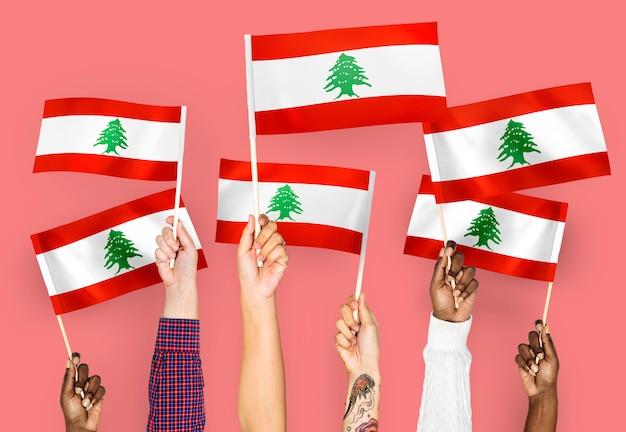 Handen met vlaggen van libanon zwaaien